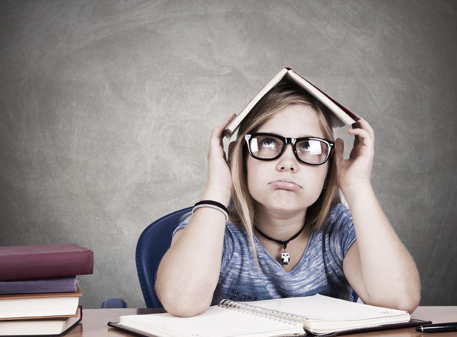 niña estudiando con cara de aburrimiento